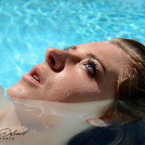 Cette photo représente une jeune femme dans de l'eau en portrait