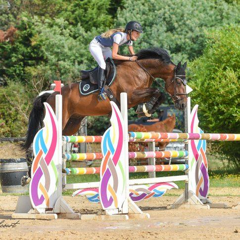 Cette photo représente une jeune femme blonde qui saute un obstacle coloré à cheval